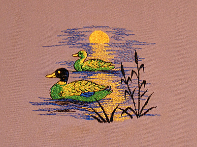 "Broderie d'un motif ""Canards"" 8 x 8 cm en 4 couleurs sur T-shirt couleur chair."